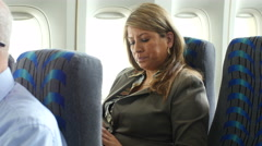 Woman using her phone on a plane Stock Footage