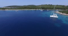 Aerial scene of bay with anchored boats, sailboats, catamarans. - stock footage