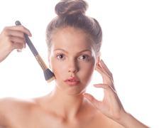 Girl with nude makeup holding makeup brush - stock photo