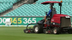 Mower is mowing the cricket grounds before the game Stock Footage