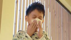 Young boy wipes his nose by tissue paper Stock Footage