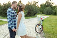 Pretty young loving couple is dating in park Stock Photos