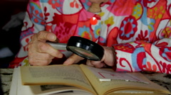 Very Old Lady Reading A Book With A Magnifying Glass, Poor Vision, Tilt Stock Footage