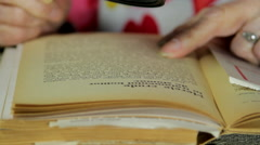 Very Old Lady Reading A Book With A Magnifying Glass, Hands Detail, Tilt Stock Footage