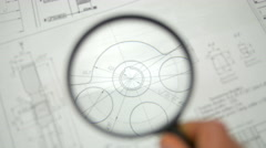 The look through loupe (magnifier) at blueprints engineering project Stock Footage