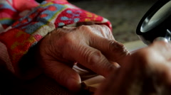 Very Old Lady Reading A Book With A Magnifying Glass, Hands Detail, Pan Stock Footage