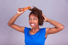 Young African American woman combing her frizzy afro hair - Black people - stock photo