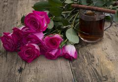 Glass of strong tea, cookies and bouquet of scarlet roses Stock Photos