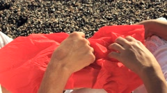 Man and Woman Open A Red Bundle Sitting on the Beach Stock Footage