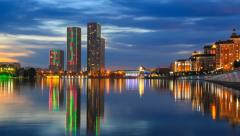Day to night view of the Yesil river with the buildings reflection in Astana Stock Footage