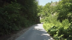 2 cars pass each of the one-lane two-way road. Rhodope Mountains, Bulgaria - stock footage