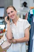 Stock Photo of Smiling woman phoning next to clothes rail