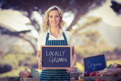 Stock Photo of Smiling farmer woman holding a locally grown sign