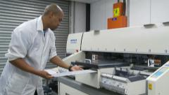 Technician loading LED panel into electronics printing machine Stock Footage