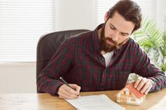 Stock Photo of Hipster businessman applying for a mortgage