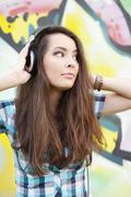 Portrait of young woman sitting at graffitti wall - stock photo