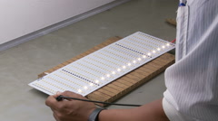 Technician testing LED strips in an electronics manufacturing plant Stock Footage