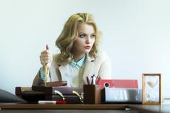 Serious woman with paper knife in office Stock Photos