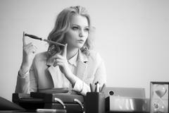 Pretty woman with paper knife in office Stock Photos