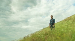 The man stand on the hill with green grass by thunderstorm sky background Stock Footage