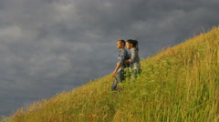 The couple stand on the hill with green grass by thunderstorm sky background Stock Footage