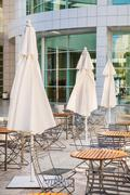 Outdoor cafe seating with round tables and white umbrellas - stock photo