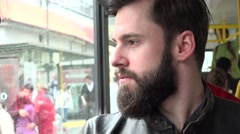 young handsome hipster man travel by tram and looks out of the window - closeup - stock footage