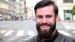 Young handsome hipster man smiles to camera - city: urban street with cars Stock Footage