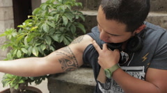 Friendly Young Man Shows Off Tattoos, Sitting in Urban Environment - stock footage