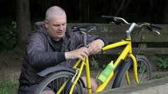 Man repairing bicycle in the park Stock Footage