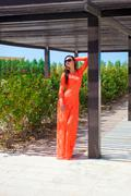beautiful young girl on vacation in orange long dress - stock photo