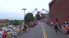 Lead runner to American Flag at finish line Stock Footage
