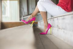 Legs and pink high heels sitting relaxed - stock photo