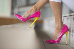 Legs and high heels sitting relaxed - stock photo