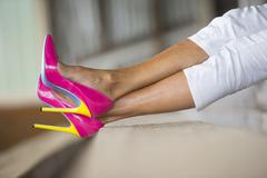 Legs and high heels lying relaxed - stock photo