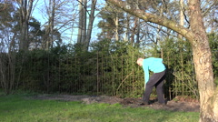 Young man dig soil with shovel for flowers along fence. 4K Stock Footage