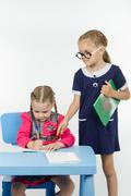 The student writes in notebook under the supervision of a teacher - stock photo