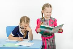 The teacher reads the student assignment - stock photo