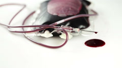 A leaking blood donation bag, needle and drops of blood Stock Footage