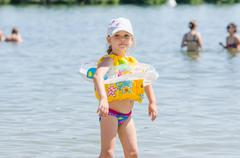 Four-year girl on the beach wearing a life jacket and circle - stock photo