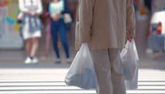 Anonymous man with shopping bags waiting to cross the street in Japan Stock Footage