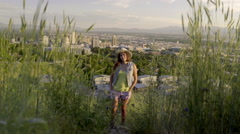 Girl Stands In Tall Grass, Salt Lake City Behind Her, She Walks Toward Camera Stock Footage