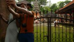 Empty yard of Pura Dalem, tourist couple make selfie against temple entrance Stock Footage
