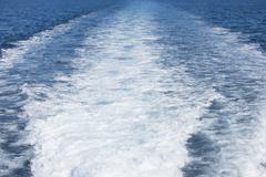 White spindrift of ship on ocean water - stock photo