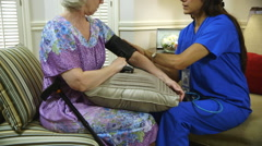 tilt up to home healthcare nurse putting on blood pressure cuff - stock footage