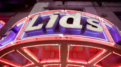 Huge Lids hat cap store sign 42nd street Times Square night people walking NYC Stock Footage