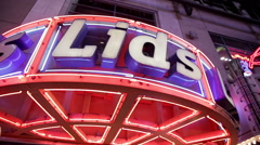 Establishing shot of Times Square stores including Lids hat store BB Kings Stock Footage