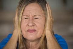 Stressed woman pain from loud sound - stock photo