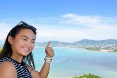 Woman tourist lifting thumb praise beautiful of sea in Phuket, Thailand - stock photo