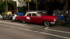 Red Chevrolet Biscayne parked at alley against restaurant on Bali Stock Footage